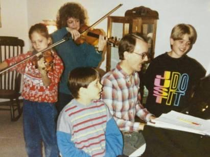 Family singing around piano